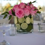 Glass container filled with limes and pink roses